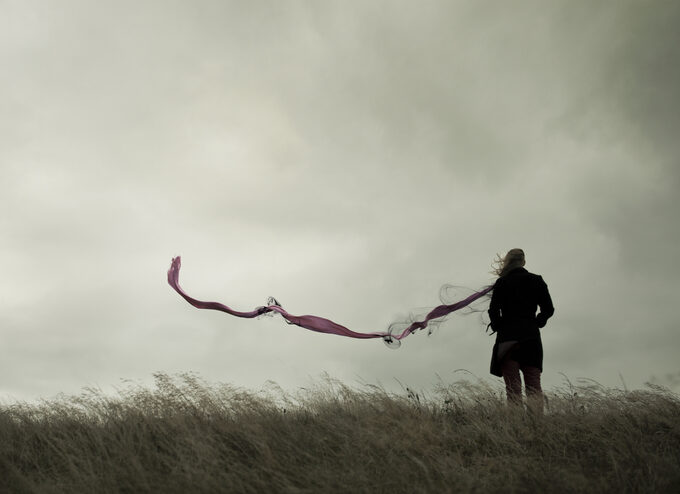 Woman standing in a field with scarf blowing in the wind