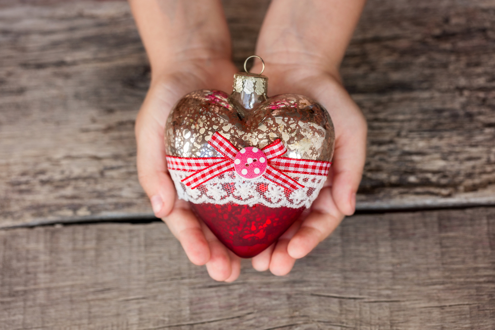 Child's hands holding Christmas heart ornament