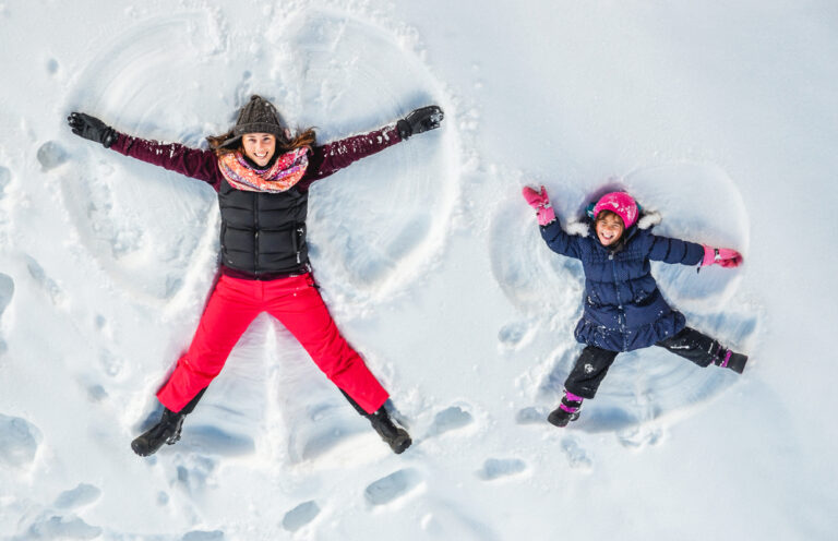 Mom and daughter making snow angel