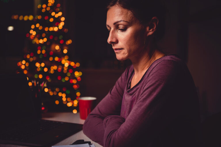 sad woman in front of Christmas tree