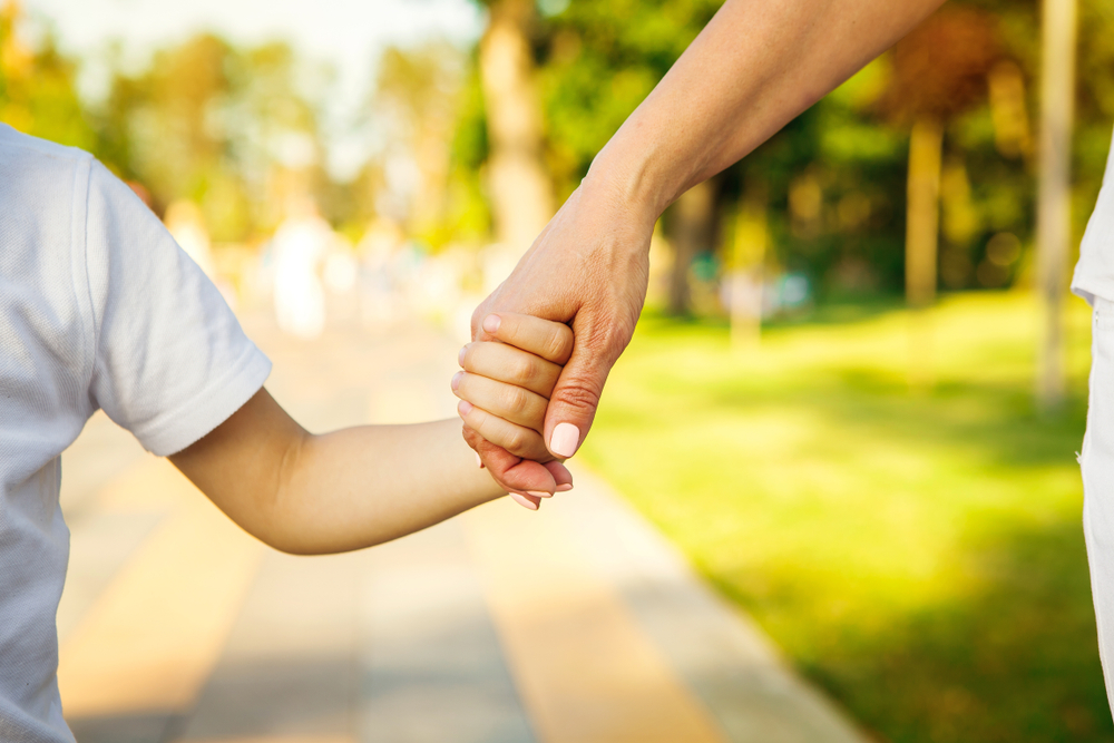 Child and woman holding hands walking