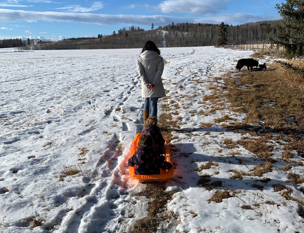 Mother pulling sled with kids