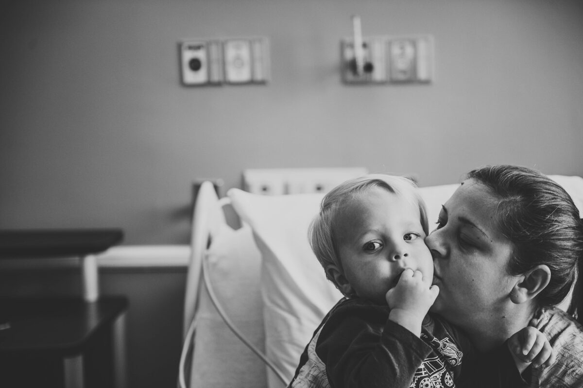 Mother kissing toddler boy on cheek, black and white photo