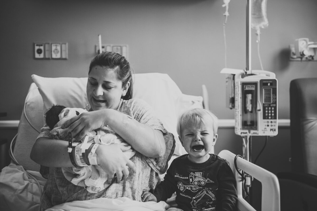 black and white photo, big brother meets baby sister and cries in hospital bed