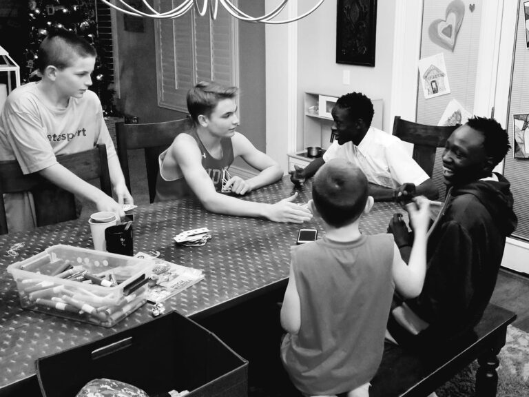 group of teenagers playing game at a table