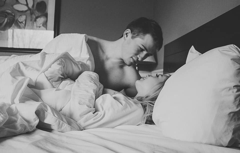 Husband and wife black and white photo smiling in bed
