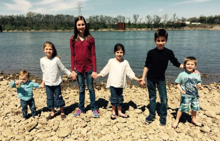 Six siblings standing by a lake holding hands