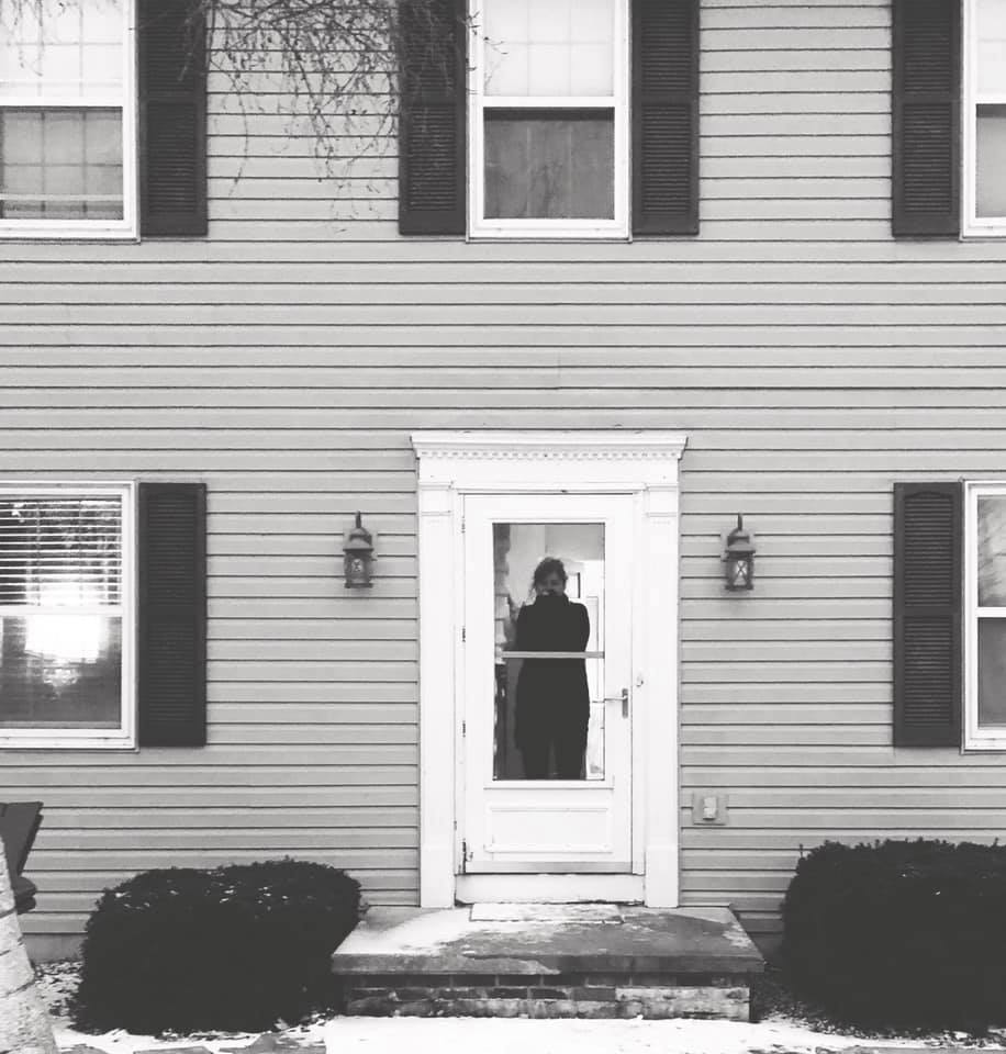 Mother standing at the door of a house, black and white photo