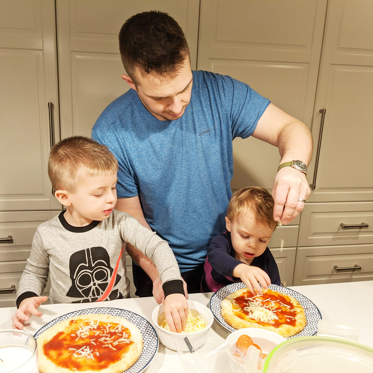 Father with two little boys cooking pizza
