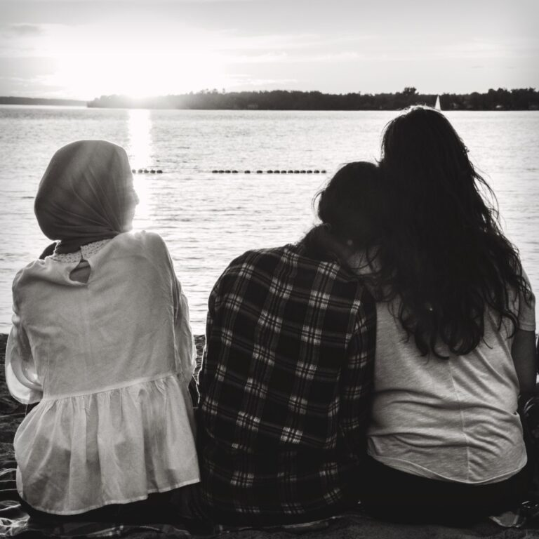 Mom sitting with daughters by a lake
