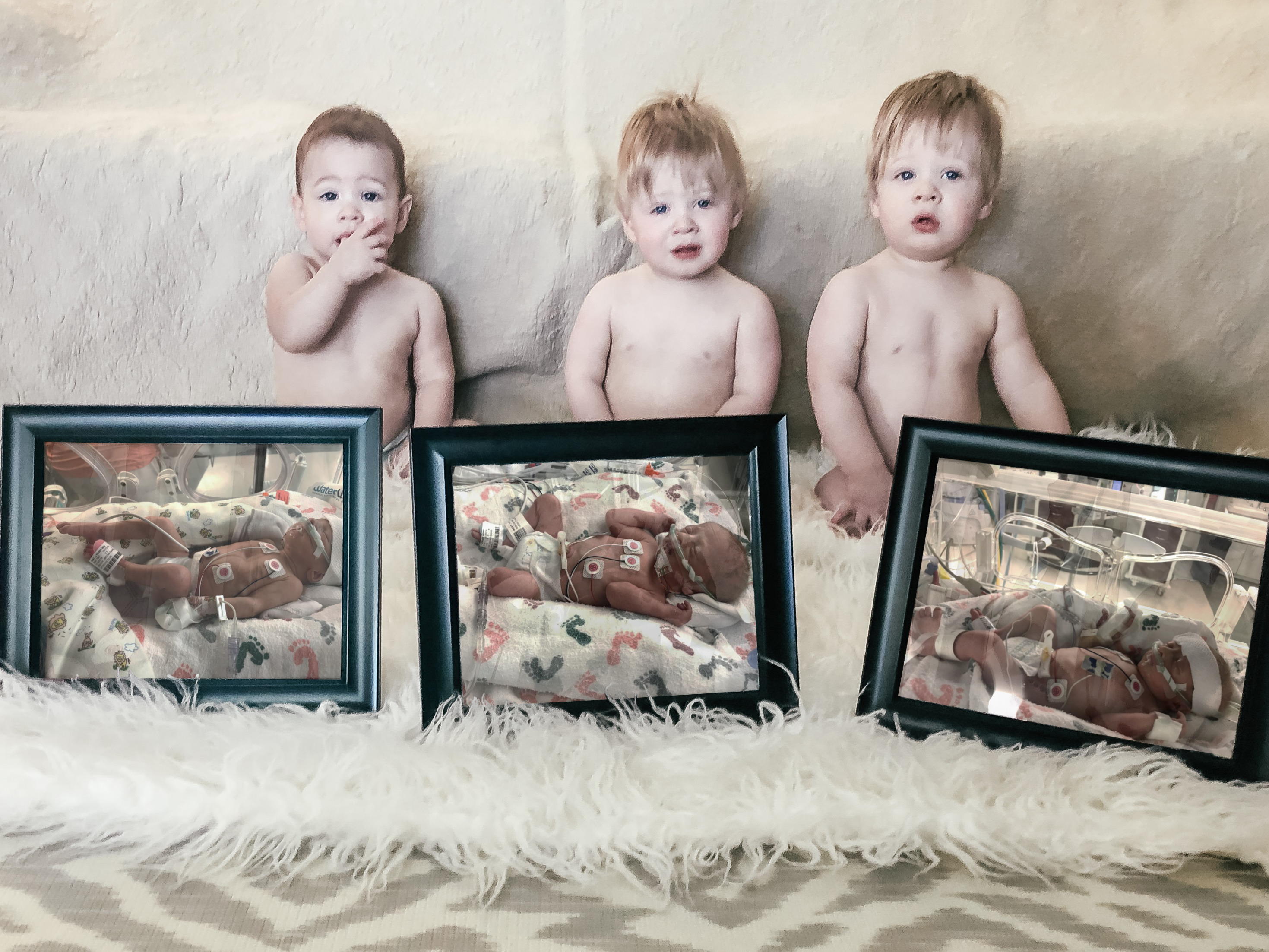 One-year-old triplets with their framed newborn pictures, color photo