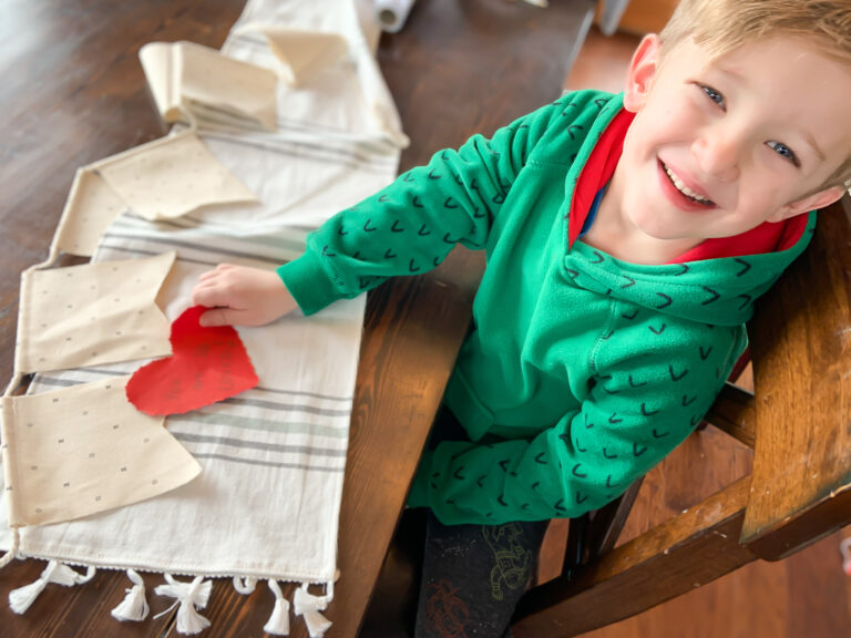 Smiling little boy with cutout hearts on table