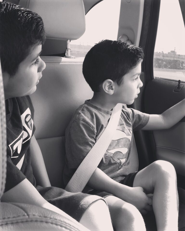 Two boys buckled in a car, color photo