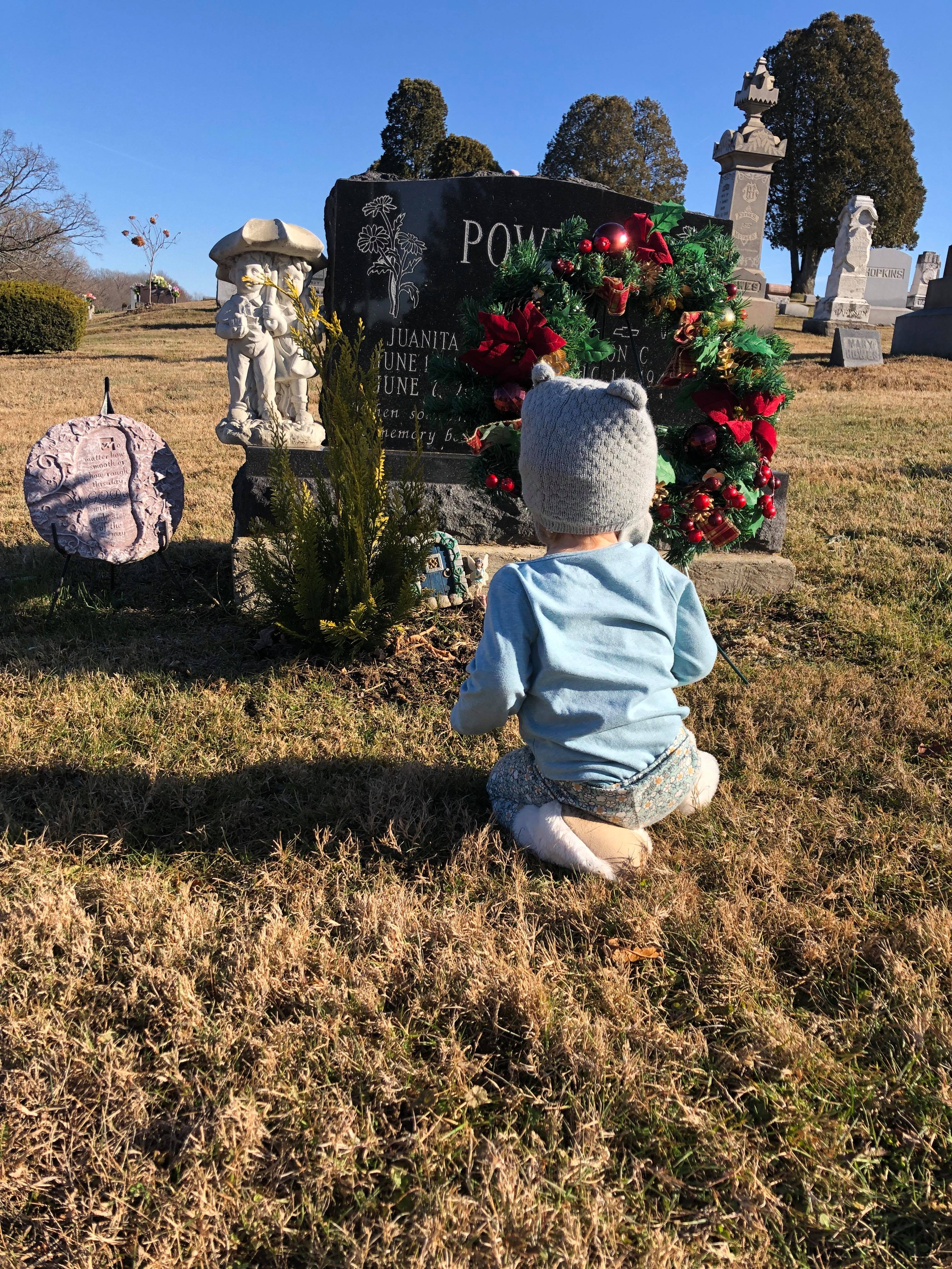 Little girl sitting in front of gradmother's grave, color photo