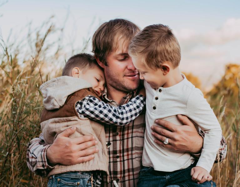 Dad hugging boys