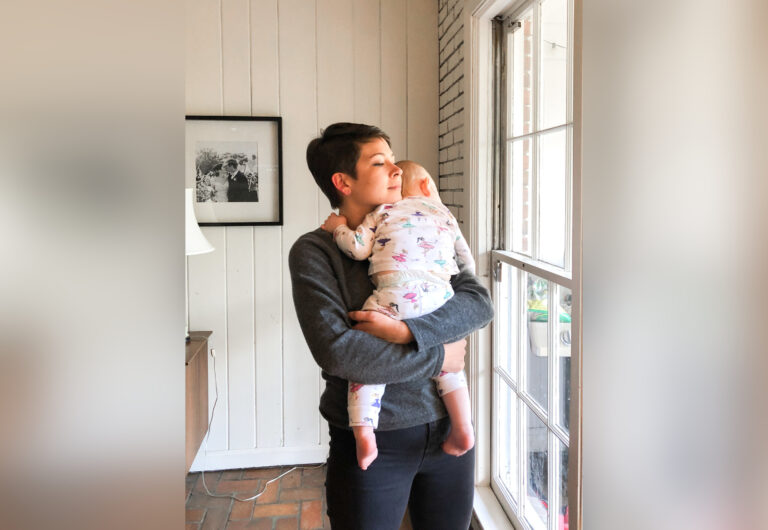 Woman holding baby looking out a window