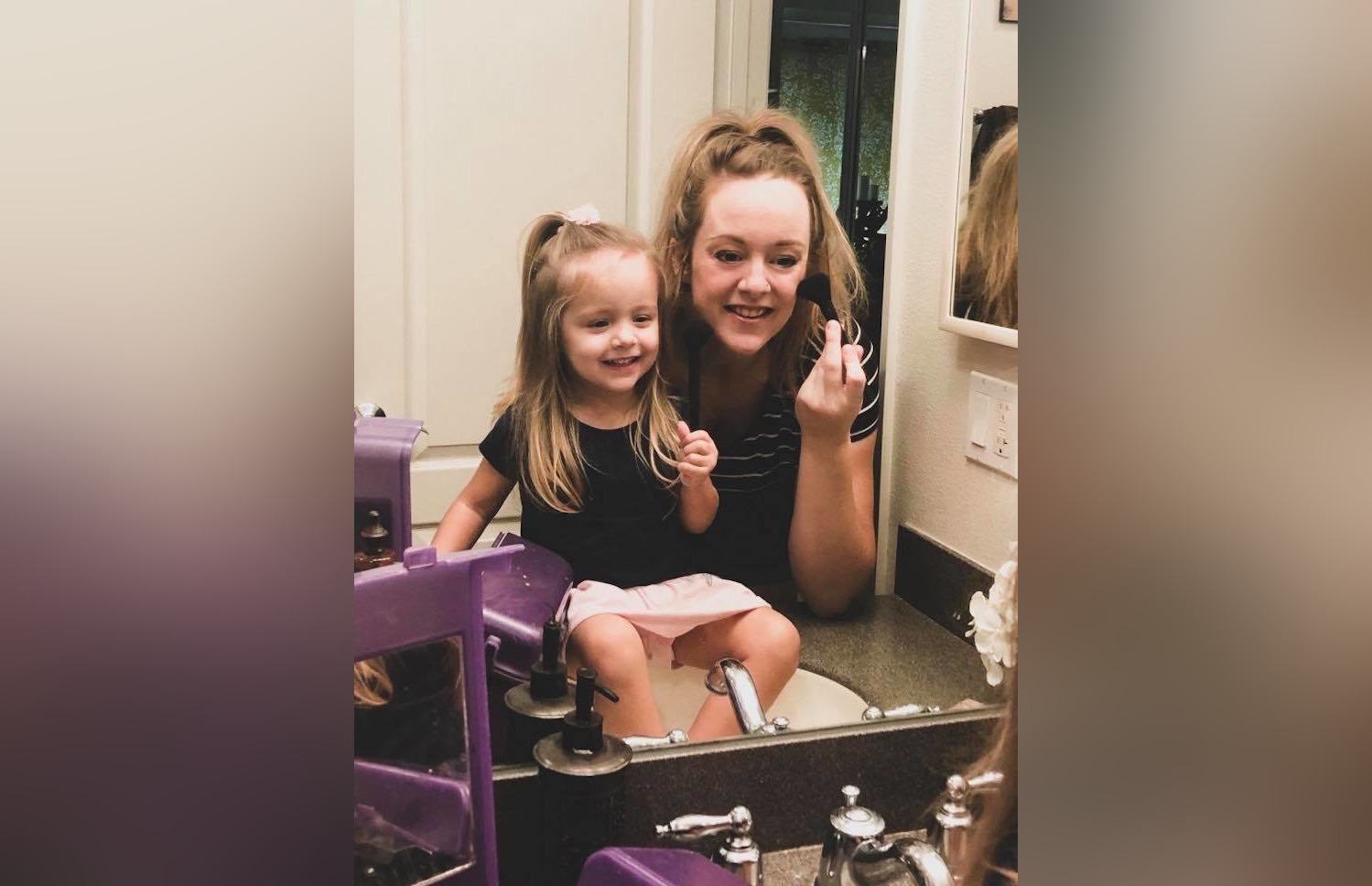 Mother and daughter putting on makeup in bathroom mirror