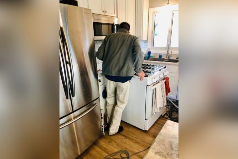 Man moving oven and vacuuming behind it