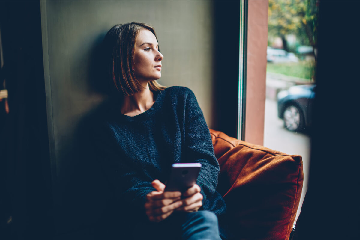 Woman holding coffee and cell phone staring out window