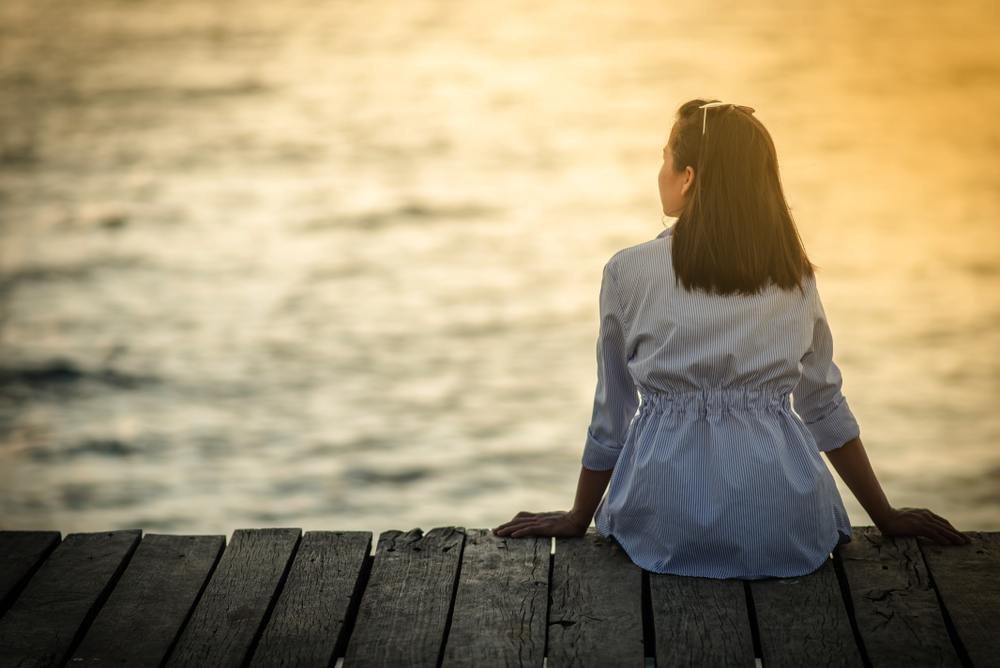 Woman sitting alone on a dock at sunset