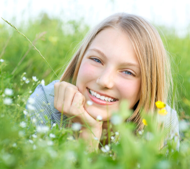 Teen girl in meadow with flowers