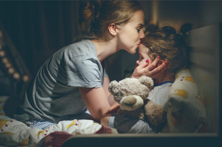 Mom kissing child at bedtime