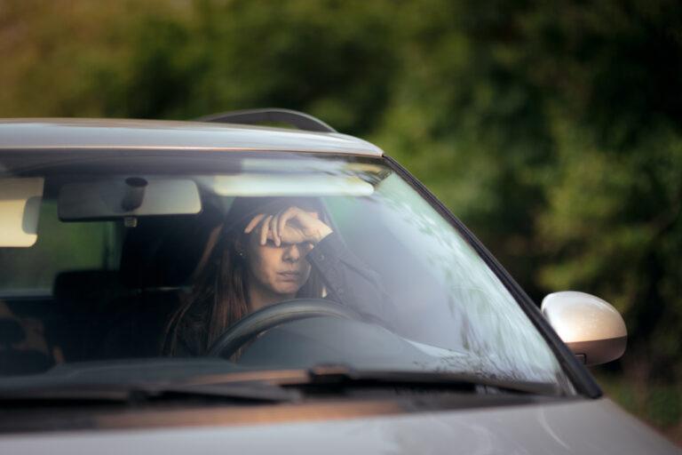 Woman feeling sad behind the wheel of car