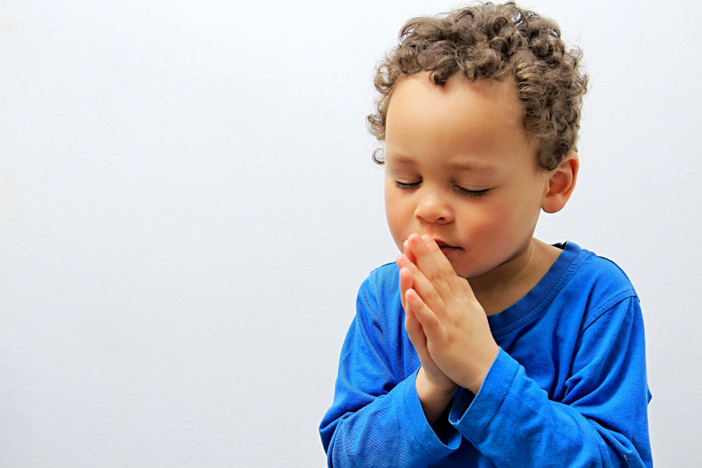 Child folding hands and praying