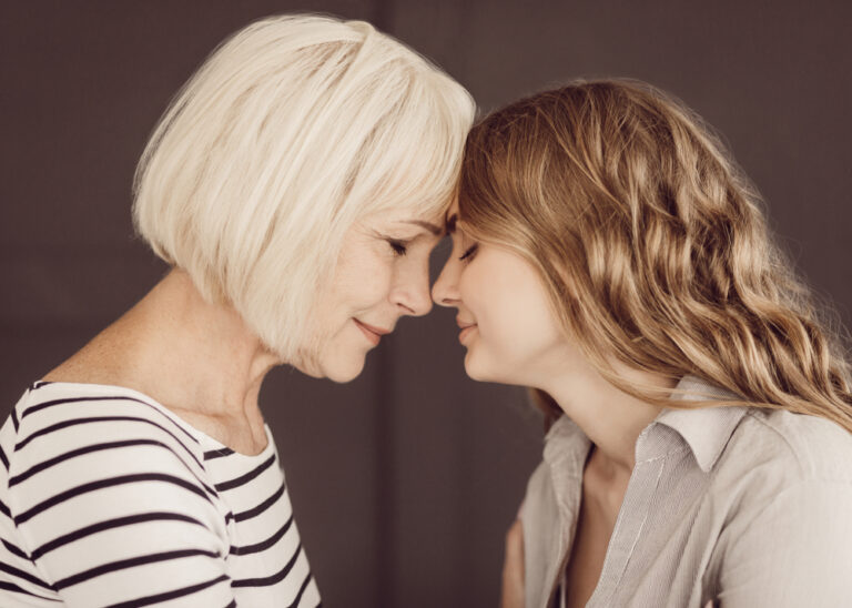 Mother and grown daughter touching foreheads