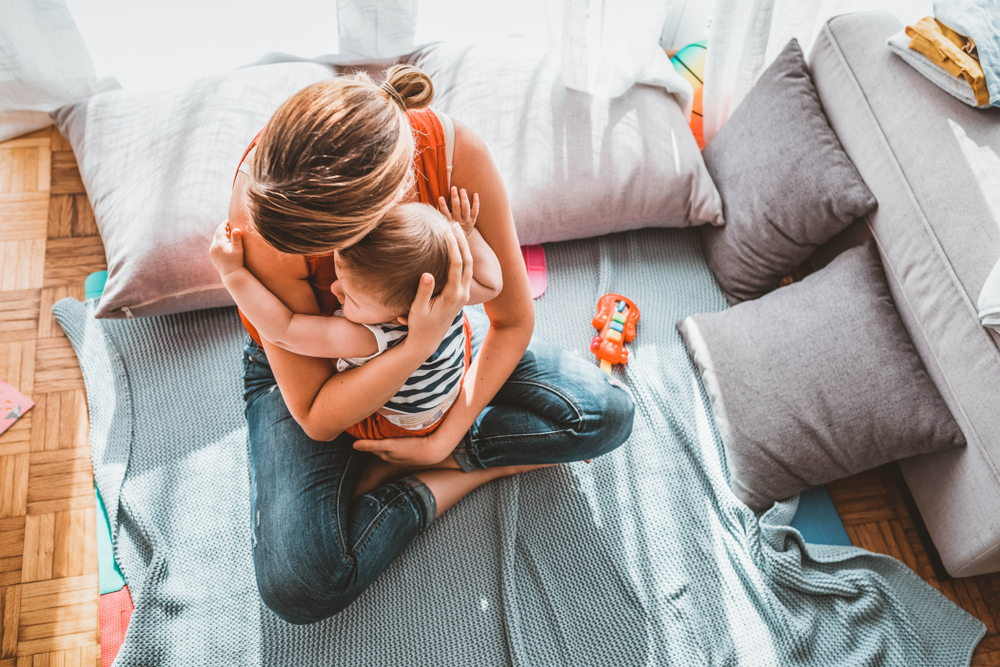 Mother hugging child in living room