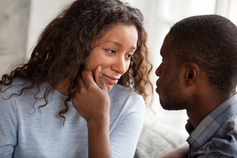 Woman looking at husband who is touching her face