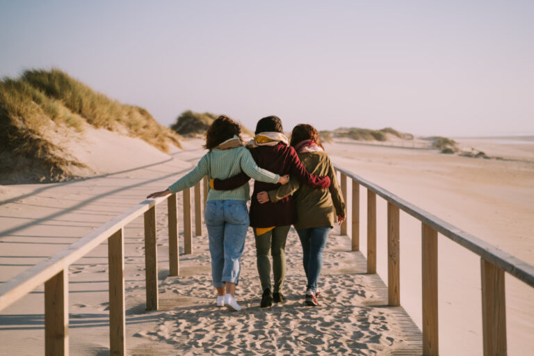 Three friends walking down boardwalk at the beach