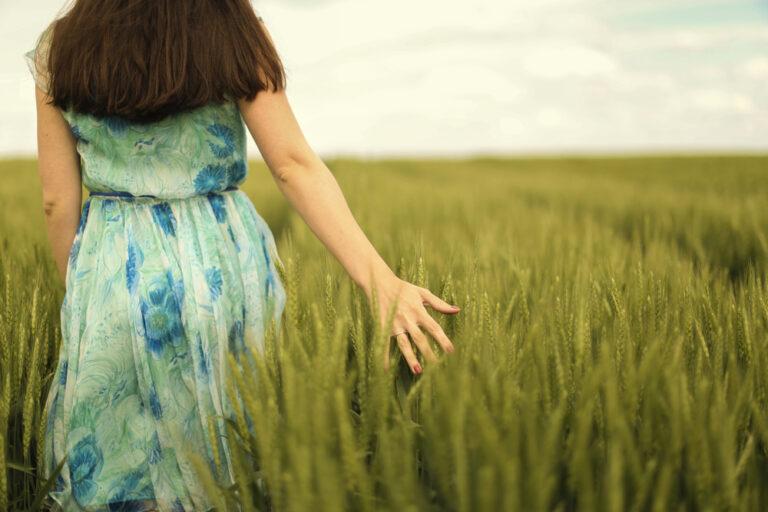 Woman trailing hand in field