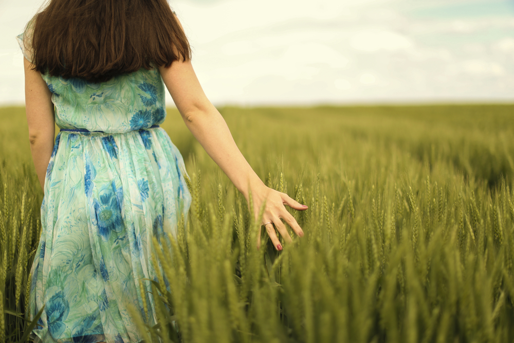 Woman trailing hand in field