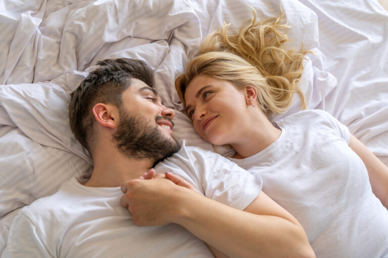 Husband and wife hold hands laying on bed