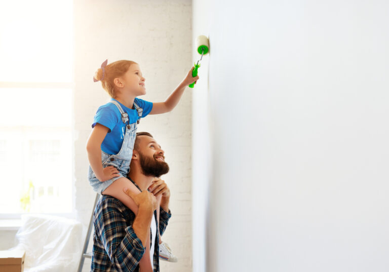 Man with child on his shoulders painting wall