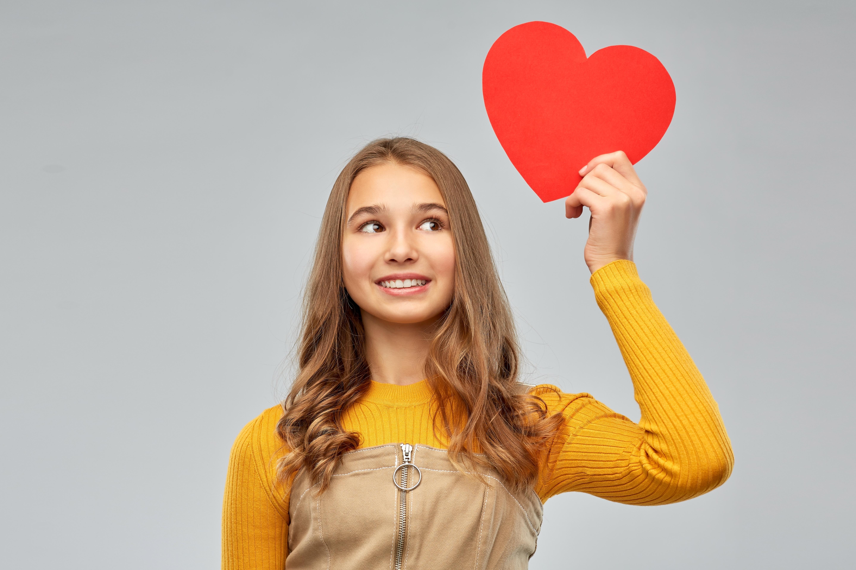 Teen girl holding paper valentine heart