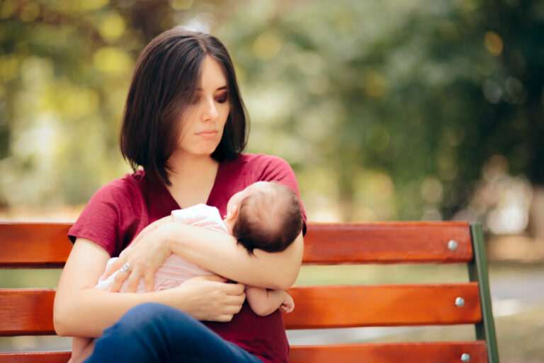 Sad woman sitting on park bench holding a baby