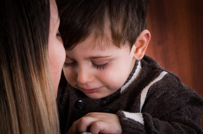 Little boy crying on his mother's lap