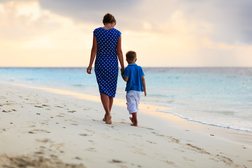 Mother and son walking on beach holding hands