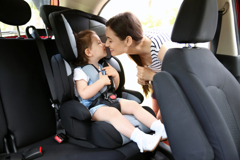 Mom touching noses with todldler in back seat of car