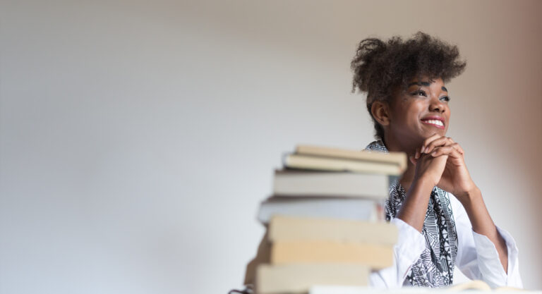 Woman sitting by stack of books