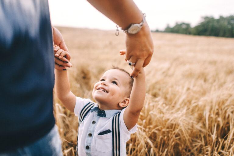 Little boy holding mother's hands