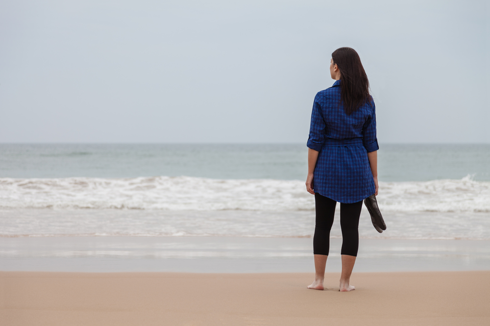Woman standing on the beach alone