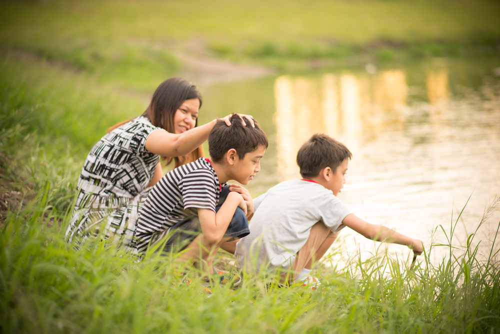 Single mother with two sons by a pond