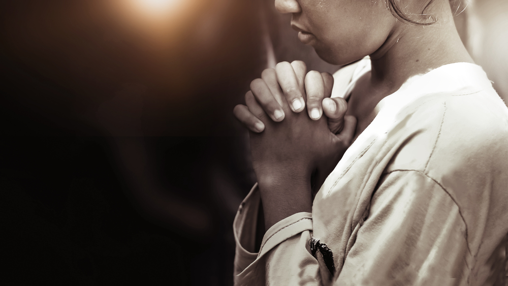 Woman hands clasped in prayer