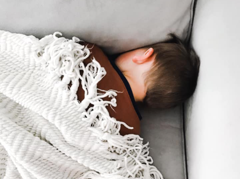 Toddler sleeping on the couch under a blanket
