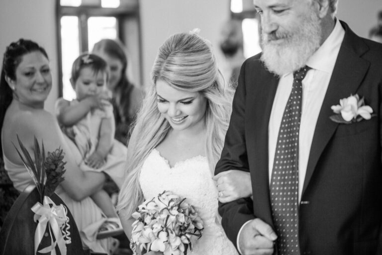 Father and daughter walking down wedding aisle