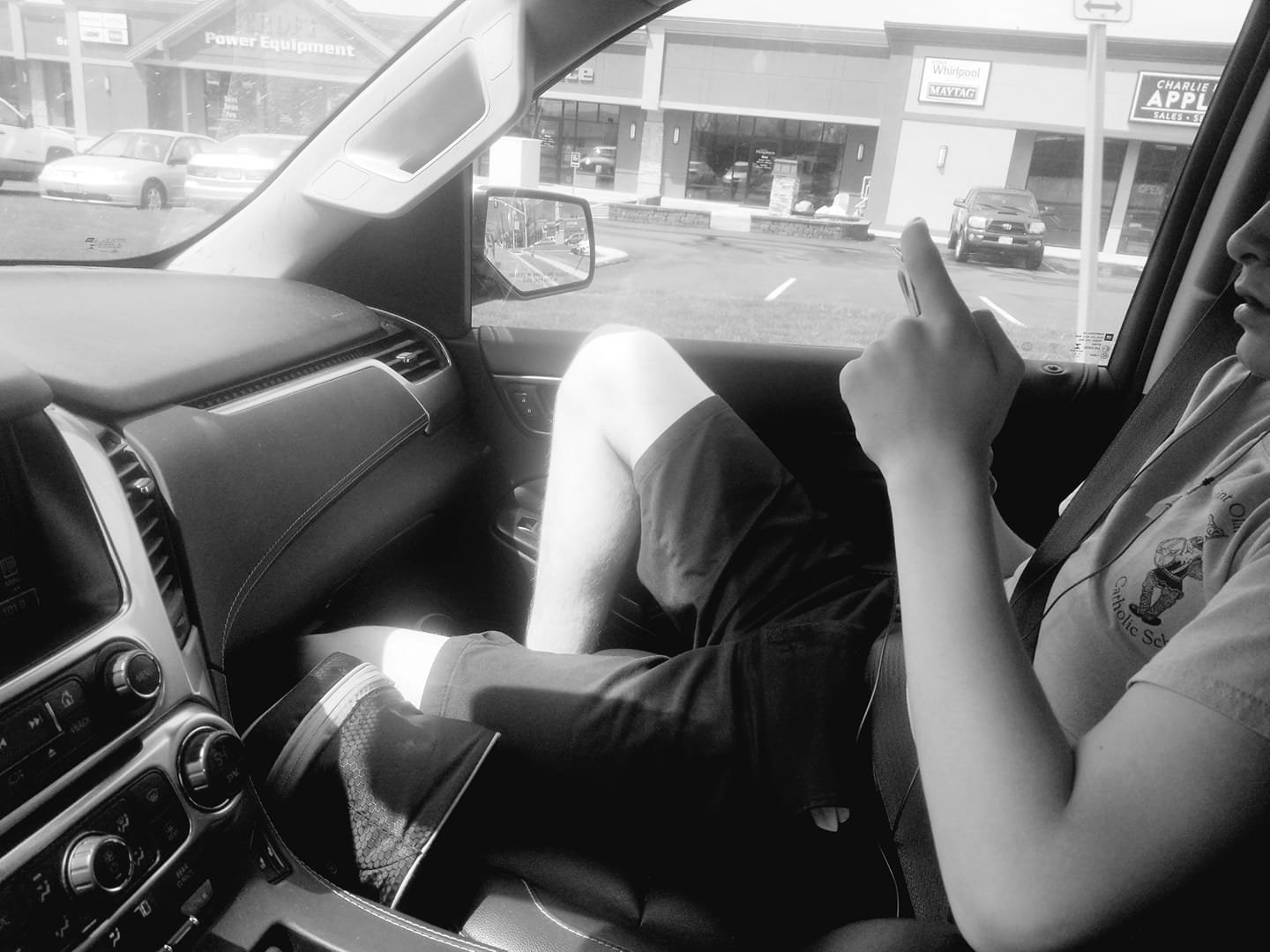 black and white photo of teen on phone in passenger seat of car