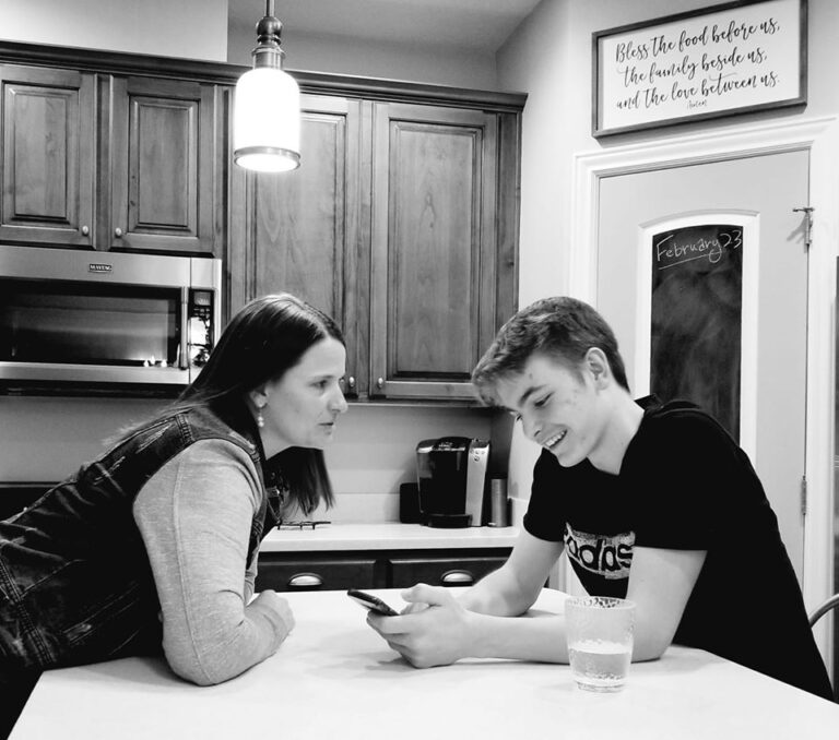 Mom and teen son on phone sit at kitchen counter